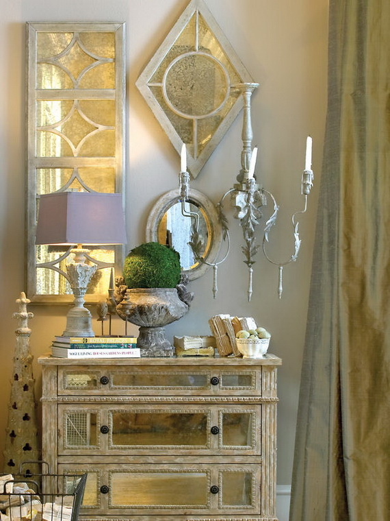 Table with lamp, decor, triangular mirror on the wall and candles.