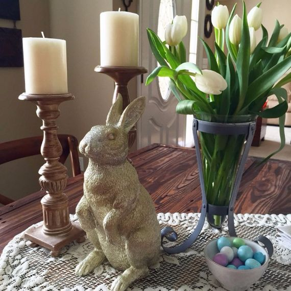 adorable-easter-holiday-decor_gold-ceramic-bunny-figurine_brown-metal-candle-stand_unique-blue-metal-vase_alluring-flower-arrangement_white-lace-table-runner-mu