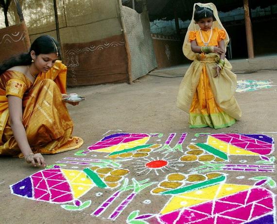 An Indian women applies coloured powder