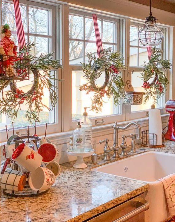 evergreen-and-berry-Christmas-wreaths-red-and-white-mugs-and-striped-ribbons-for-a-holiday-feel