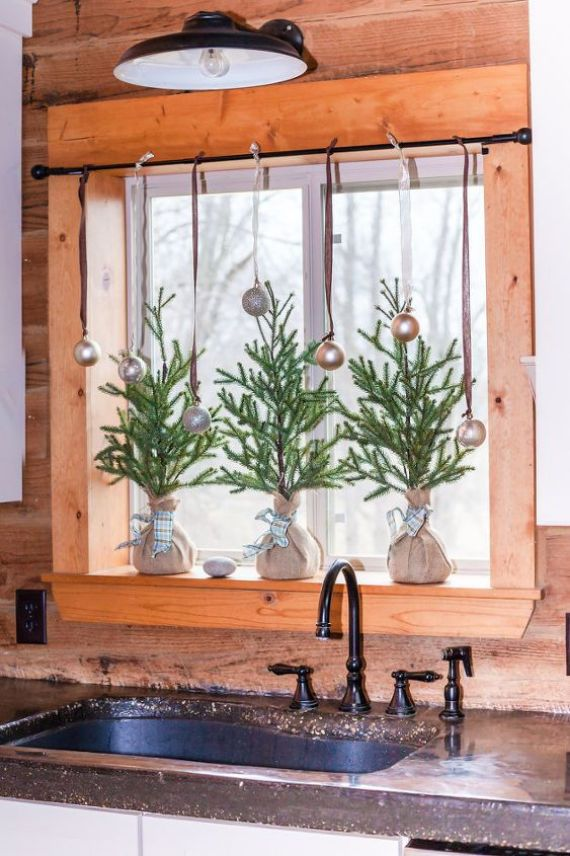 mini-Christmas-trees-in-burlap-and-metallic-ornaments-on-the-window-for-a-holiday-feel-in-the-space