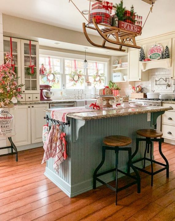 red-grey-and-white-Christmas-kitchen-decor-a-sleigh-over-the-kitchen-island-printed-linens-and-a-mini-Christmas-tree
