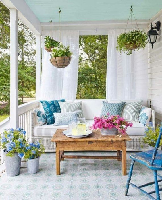 a-colorful-spring-porch-with-potted-greenery-and-blooms-printed-pillows-and-vintage-furniture