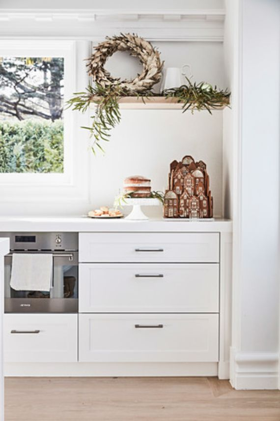 Winter-decorative-wreath-on-kitchen-shelf-including-gingerbread-house-and-pastries